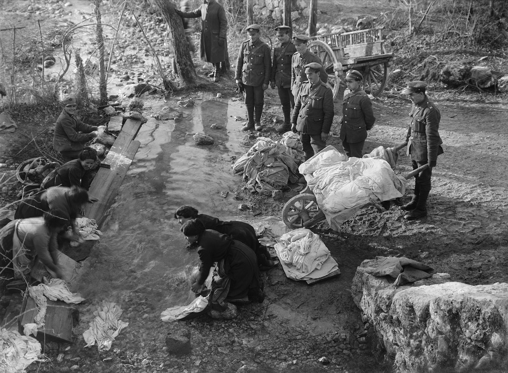 Ernest Brooks, Men of the Royal Engineers watch as their clothes are washed in a stream by Italian peasant women, Novemmer-December 1917, courtesy: Imperal War Museum